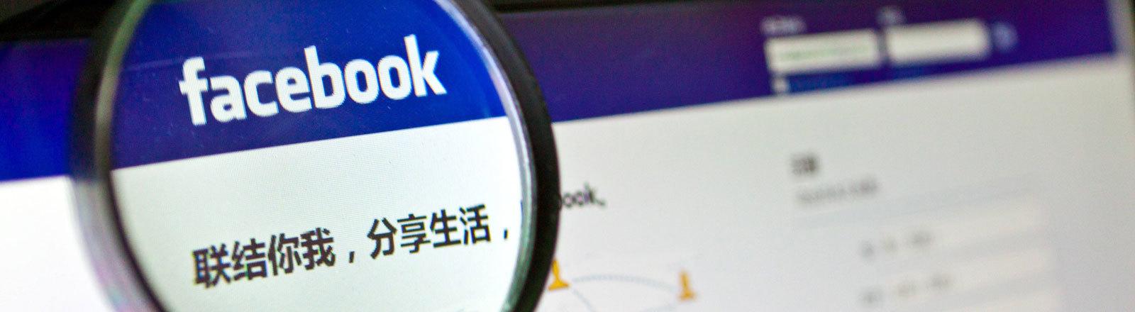 Lupe zeigt auf Facebook-Logo auf der Facebook-Website, aufgerufen in China im Jahr 2012