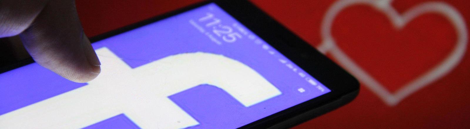 Smartphone mit Facebook-Logo und Herzen im Hintergrund