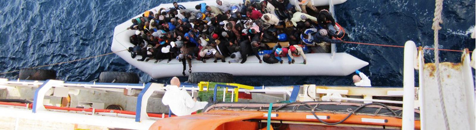"""Die Aufnahme vom 05.02.2015 zeigt ein Flüchtlingsboot neben dem Frachtschiff """"OOC Cougar""""."""