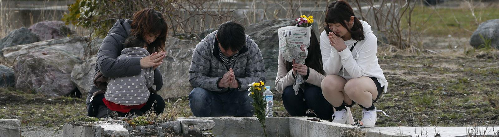 Drei Frauen trauern in unmittelbarer Nähe des Reaktors Fukushima um Angehörige.