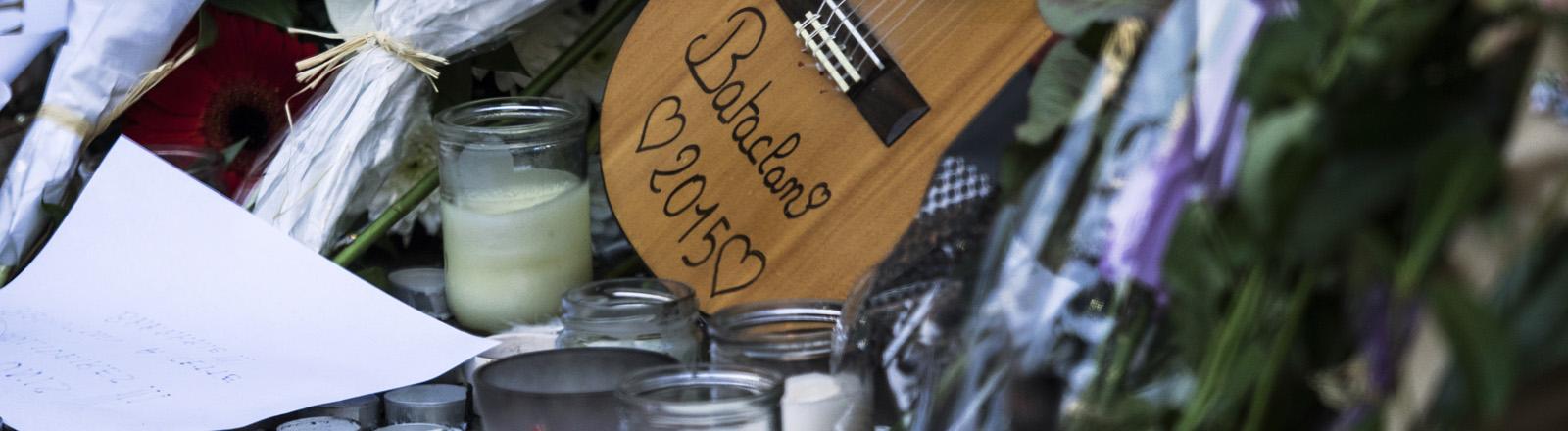 Blumen, Kerzen und eine Gitarre liegen zum Gedenken an die Opfer der Terroranschläge in der Nähge des Musiktheaters Bataclan