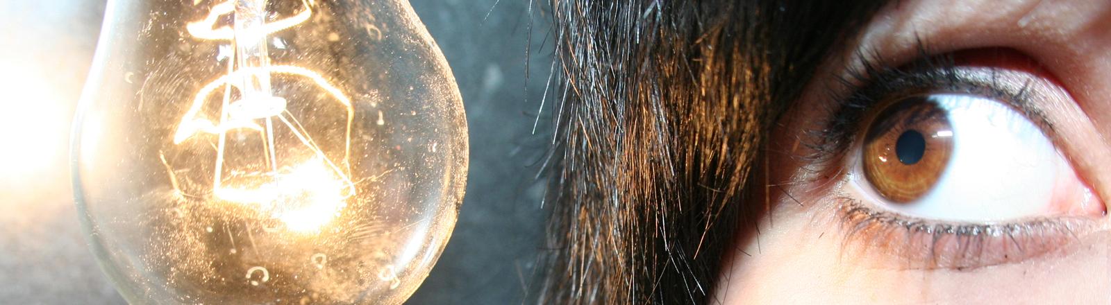 Eine Frau schaut in eine Glühbirne