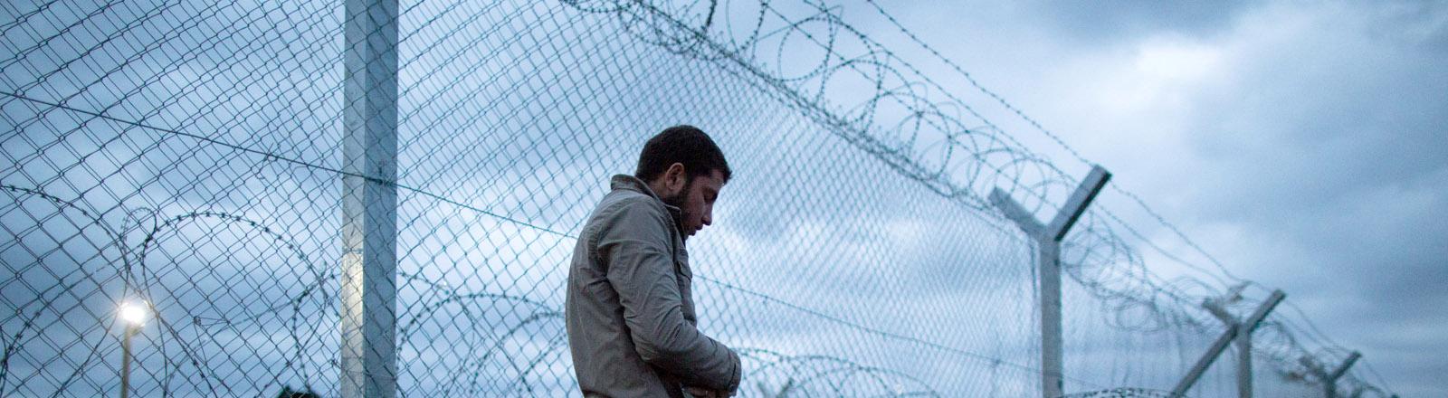 Ein Mann betet am 07.03.2016 im Flüchtlingslager in Idomeni an der Grenze zwischen Griechenland und Mazedonien zwischen Stacheldrahtrollen am Grenzzaun.