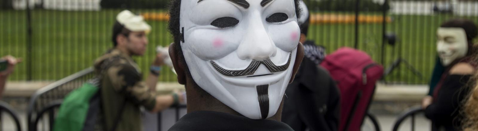 Ein Mann mit einer Guy-Fawkes-maske vor dem Weißen Haus