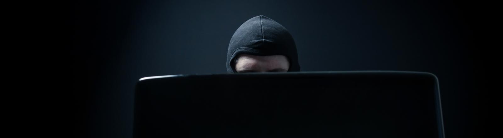Ein Mann mit Maske sitzt vor einem Rechner