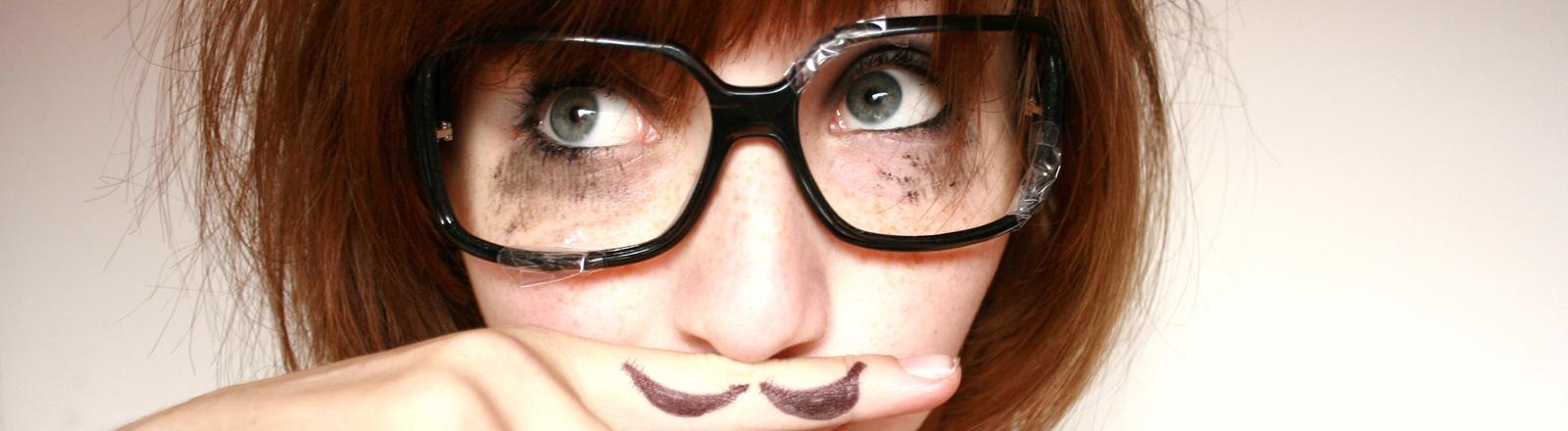 Eine Frau mit Brille hält sich einen Finger mit aufgemaltem Schnurbart an den Mund.
