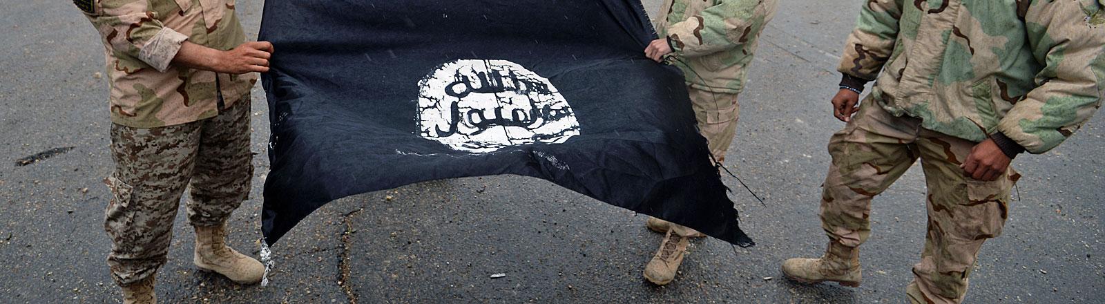 IS-Flagge wird von Soldaten gehalten, die man nicht erkennt