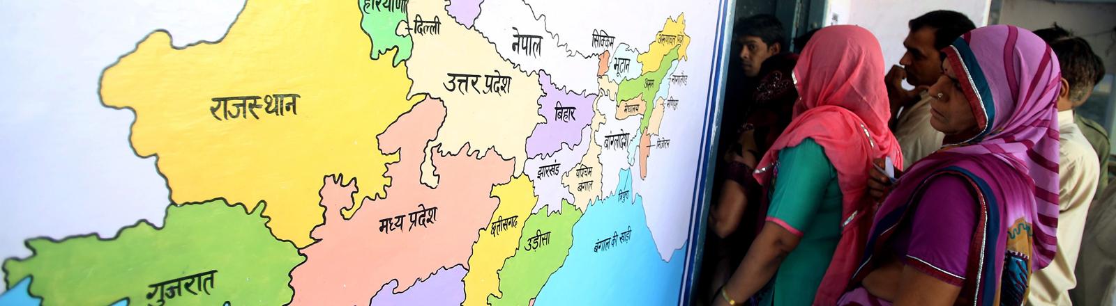 Wähler neben einer Karte von Indien in Tigaon im Staat Haryana