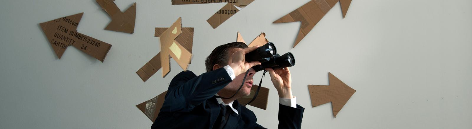 Ein Mann mit Fernglas. Hinter ihm sind Pfeile zu sehen