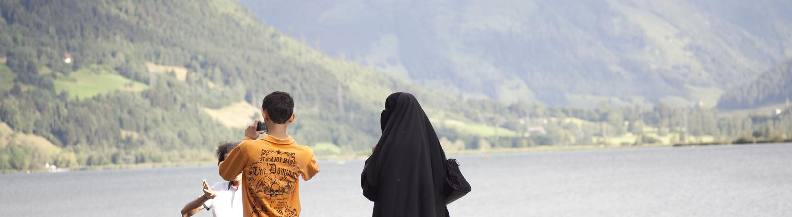 Eine verschleierte Touristin aus einem arabischen Land ist mit ihrer Familie am Seeufer in Zell am See im Bundesland Salzburg in Österreich zu Fuß unterwegs.