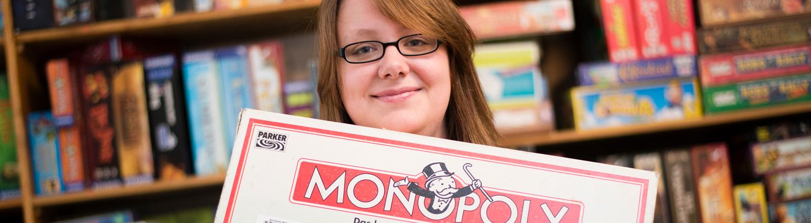 Die amtierende Deutsche Meisterin im Monopoly, Ita Hoffmann posiert am 23.08.2015 mit einem Monopoly-Spiel im Cafe Spielwiese in Berlin, für ein Portrait.