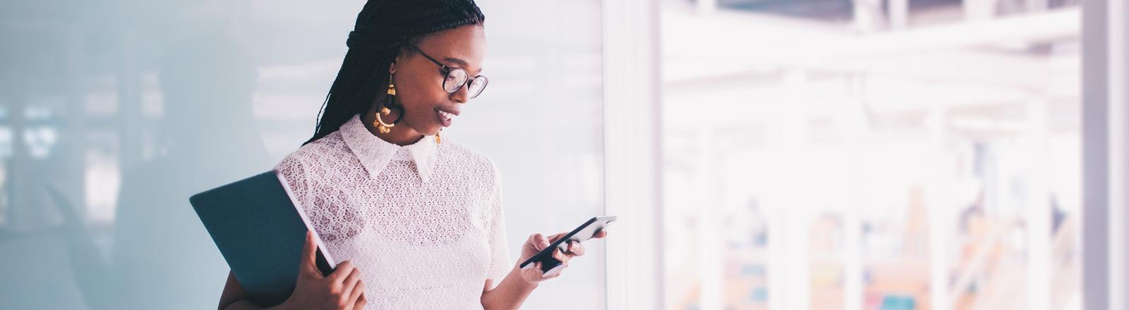 Eine junge Frau mit Smartphone im Business-Outfit
