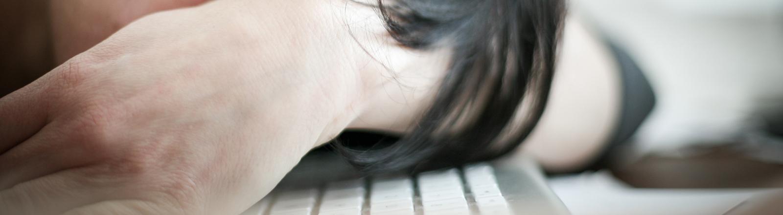 Ein Frau legt den Kopf neben ihre Tastatur