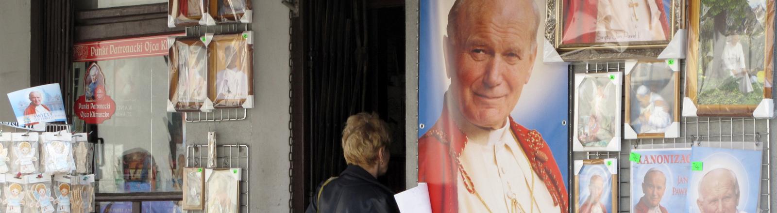 Eine Frau geht am 09.04.2014 in Wadowice (Polen) in ein Devotionaliengeschäft. Hier kann sich der Wojtyla-Fan mit allem ausstatten, was zum Kult um den polnischen Papst Johannes Paul II. gehört.