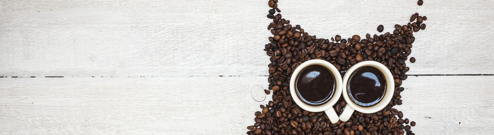 Eine Eule aus Kaffeebohnen und zwei Espressotassen