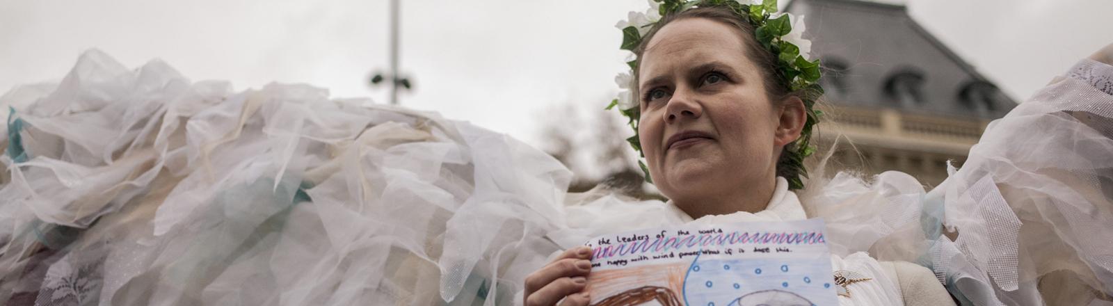 Eine Demonstrantin gegen den Klimagipfel in Paris trägt ein Engelskostüm