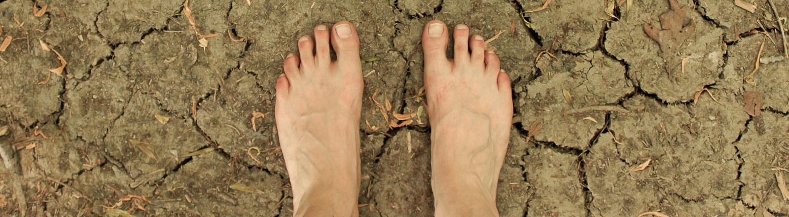 Nackte Füße auf ausgetrockneter Erde