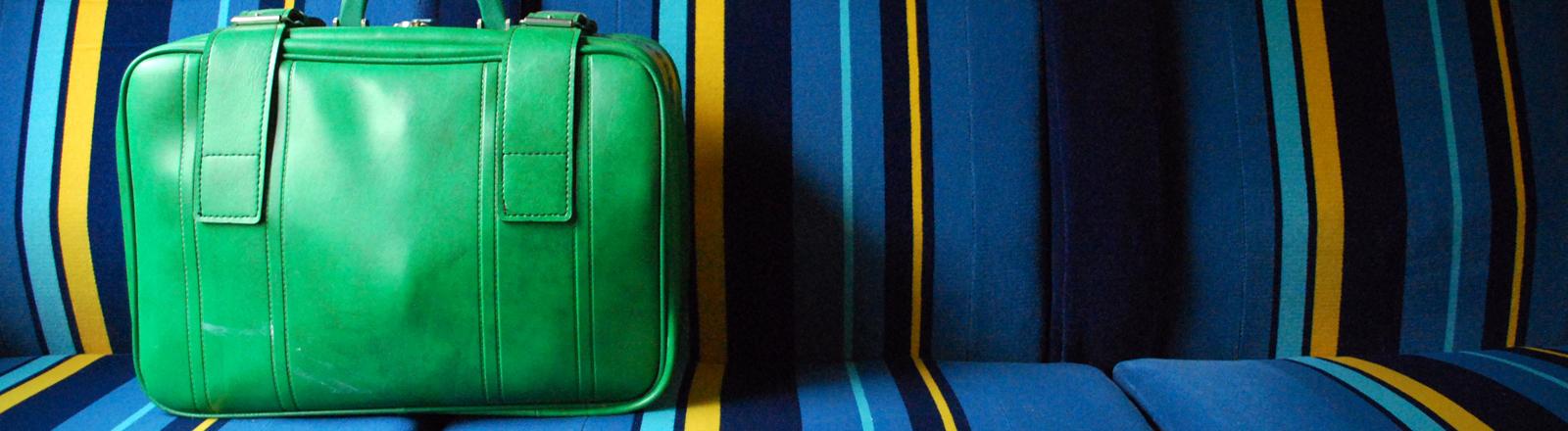 Ein grüner Koffer auf einer Sitzbank