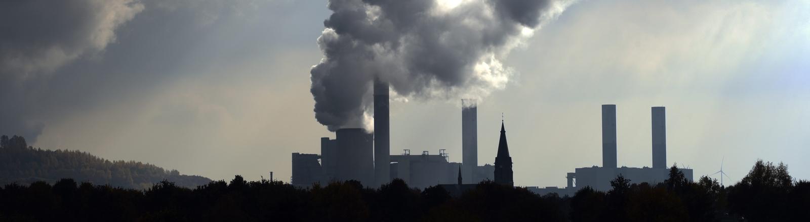 Bedrohlich wirken im Gegenlicht die Dampfwolken die aus dem Kühlturm des RWE-Braunkohlekraftwerks Frimmersdorf in Greverbroich (Nordrhein-Westfalen) steigen und über der kleinen Ortschaft Gustorf mit der katholischen Kirche St. Maria Himmelfahrt (M) hängen.