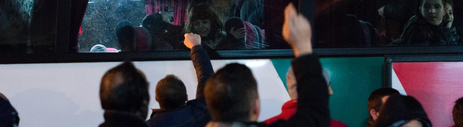 Männer verabschieden sich am Busbahnhof in Pristina von Verwandten