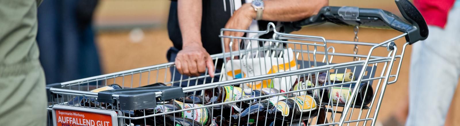 Ein Flaschensammler steht am 05.06.2014 in Erlangen (Bayern) während der Bergkirchweih neben einem Einkaufswagen voller Flaschen.