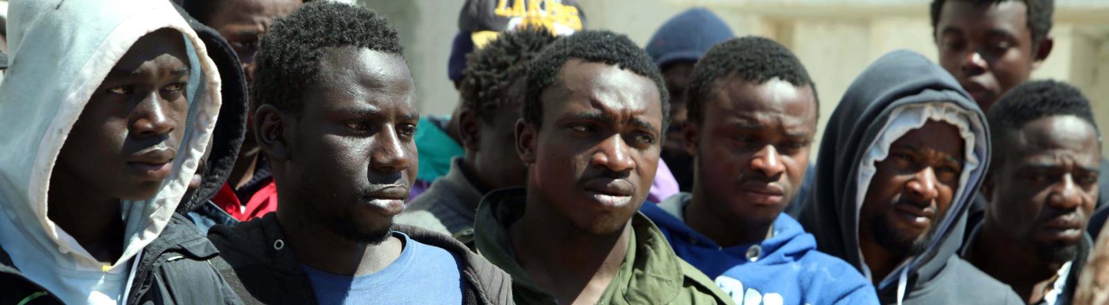 Flüchtlinge warten darauf, in ein Gefängnis in Triplois überführt zu werden.