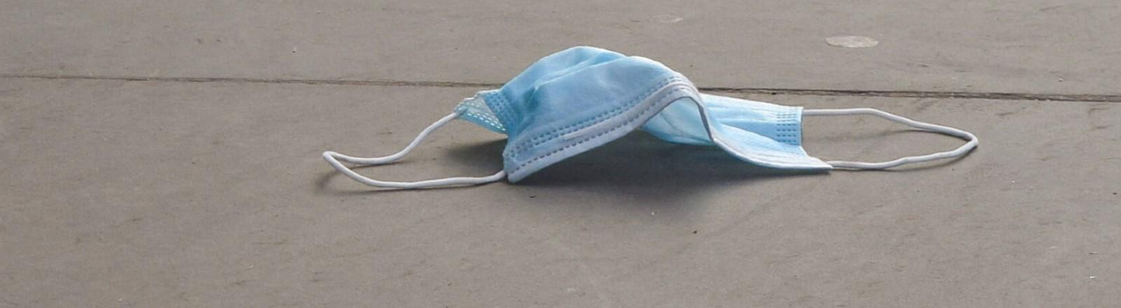 Eine blaue OP-Maske liegt in London auf der Straße