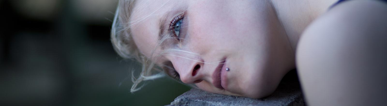 Ein junge Frau hat den Kopf auf einen Balken gelegt