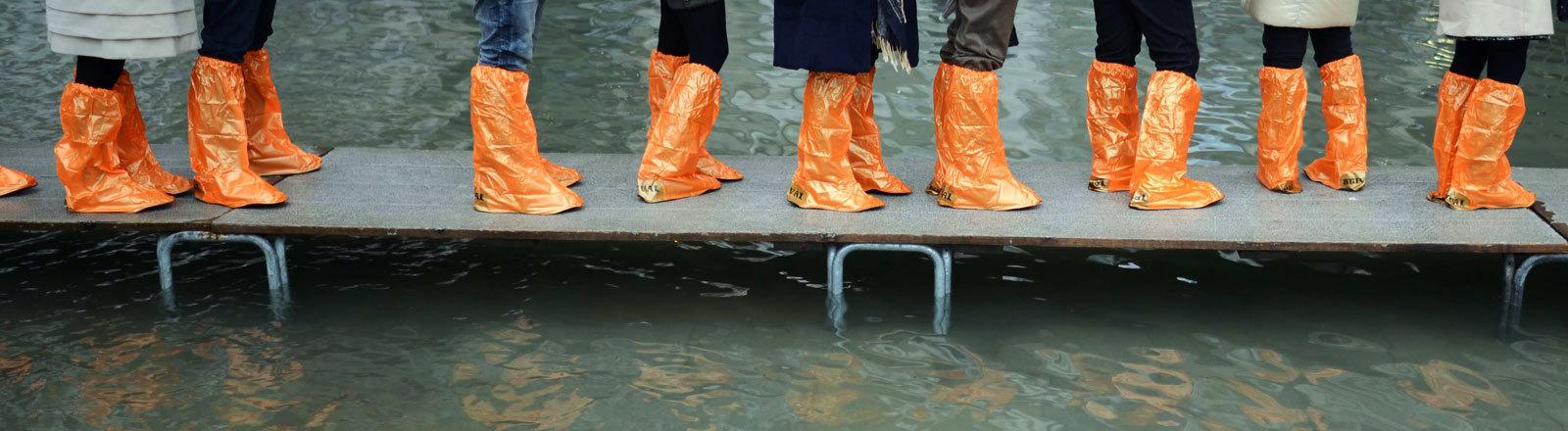 Menschen stehen in Gummischuhen auf einem Steg in Venedig, während dort Hochwasser herrscht.
