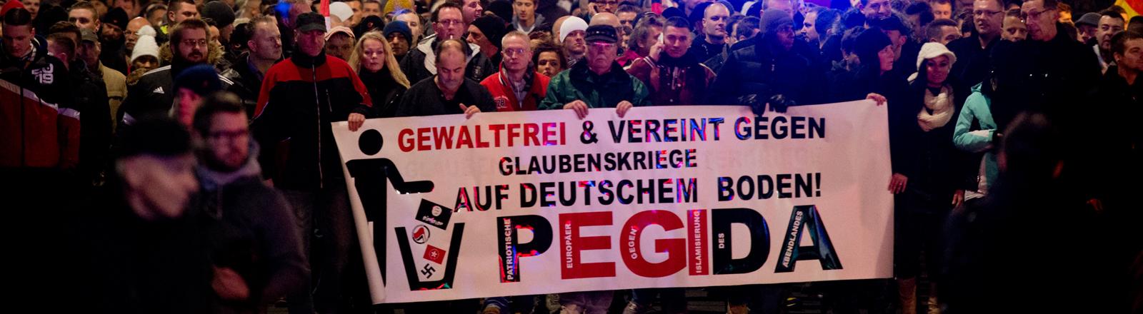 Teilnehmer einer Kundgebung der Pegida beteiligen sich am 15.12.2014 an einer Kundgebung in Dresden (Sachsen).