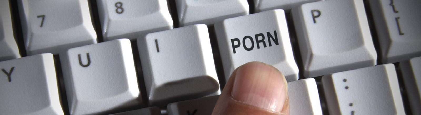 """Ein Finger drückt auf einer Tastatur auf eine Taste mit der Aufschrift """"porn"""""""