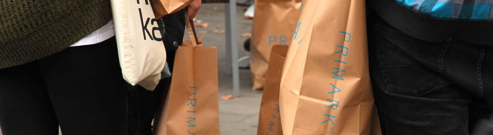 Junge Leute tragen Papiertüten der Textilkette Primark in Berlin im Bezirk Steglitz am 27.09.2013.