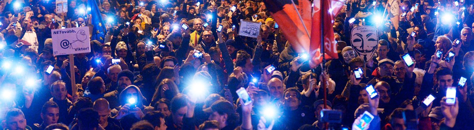 Menschen protestieren auf der Straße und halten ihr Handy in die Kamera