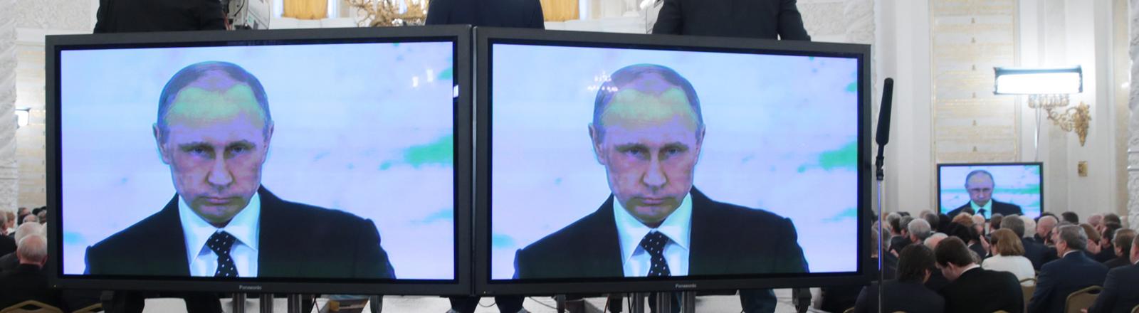 Wladimir Putin ist bei einer Rede auf Bildschirmen zu sehen.