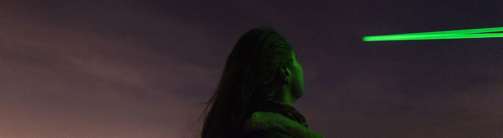 Frau schaut in den Nachthimmel, an dem grüne Lichtbahnen zu sehen sind