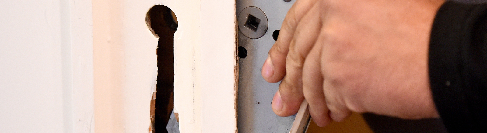 Ein Mitarbeiter eines Schlüsseldienstes baut am 26.08.2014 in Langenhagen (Region Hannover, Niedersachsen) ein defektes Türschloss aus.