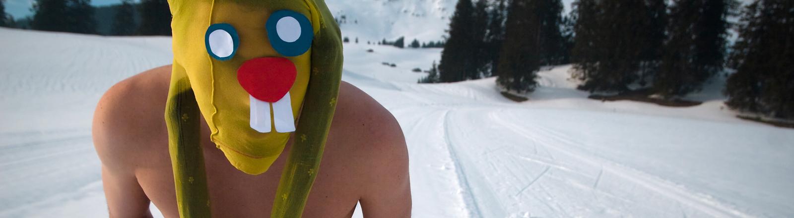 Ein nackter Mann mit Hasenmaske im Schnee
