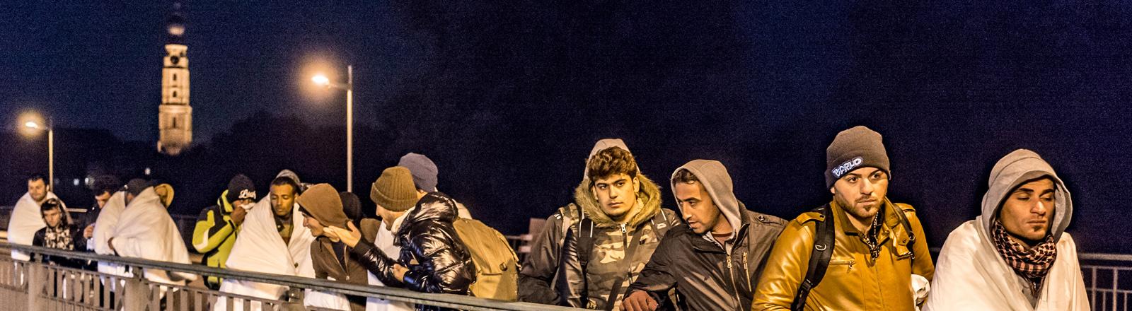 Flüchtlinge warten am 25.10.2015 auf der Innbrücke an der deutsch-österreichischen Grenze zwischen Simbach am Inn (Bayern) und dem österreichischen Braunau.