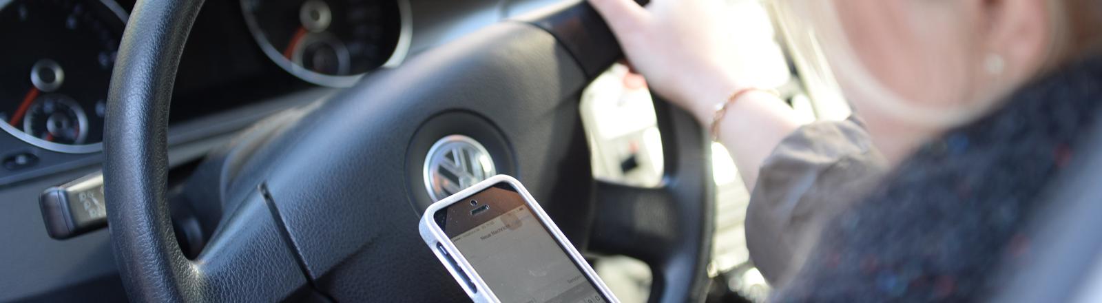Eine Frau schaut im Auto auf ihr Smartphone