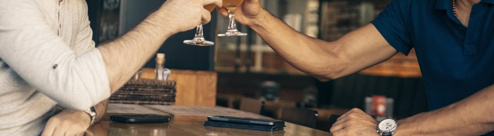Zwei prosten sich in einer Bar zu. Vor ihnen liegen Smartphones