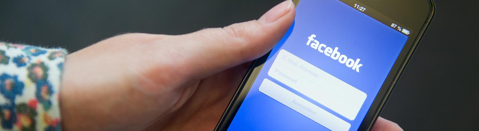 Eine Frau hält am 11.09.2014 in Berlin ein iPhone mit der geöffneten Facebook App in ihrer Hand.