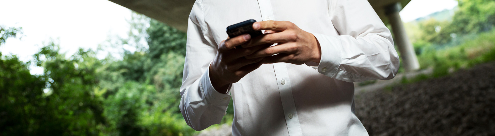 Ein junger Mann tippt auf seinem Smartphone
