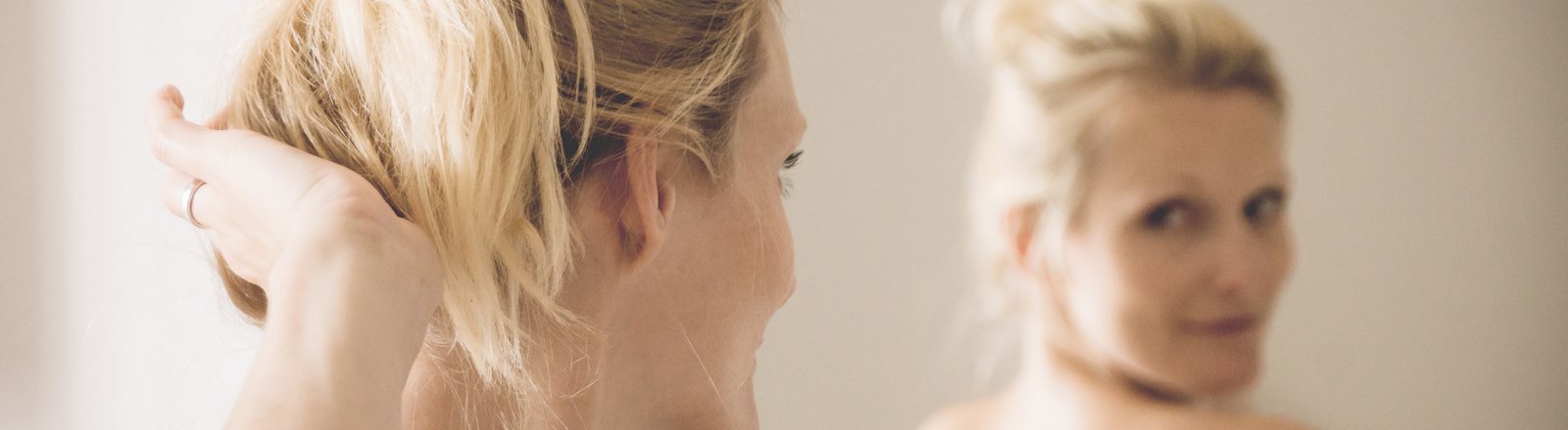 Eine freu betrachtet ihr Spiegelbild