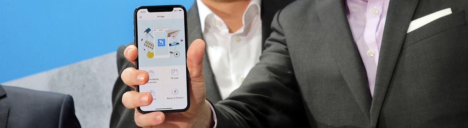 """24.04.2018, Berlin: Jens Baas (r), Vorsitzender des Vorstands der Techniker Krankenkasse und Matthias Hartmann, Geschäftsführer IBM Deutschland, präsentieren eine App zum Start einer ersten """"Elektronischen Gesundheitsakte""""."""