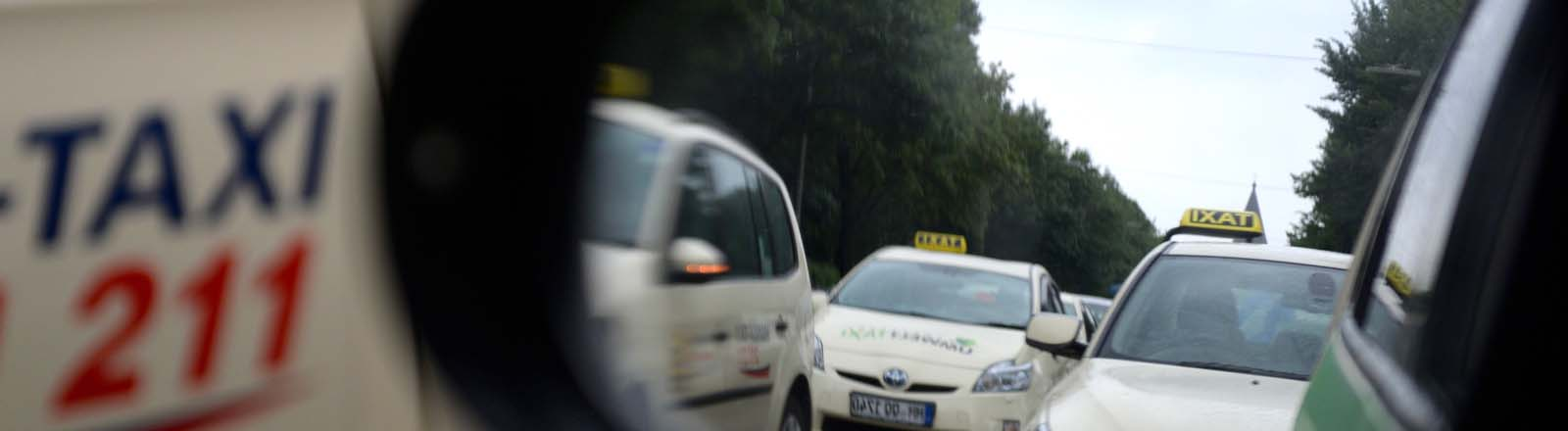 Taxis sind am 11.06.2014 in Hamburg vor einer Protestfahrt durch die Innenstadt im Außenspiegel eines anderen Taxis zu sehen.
