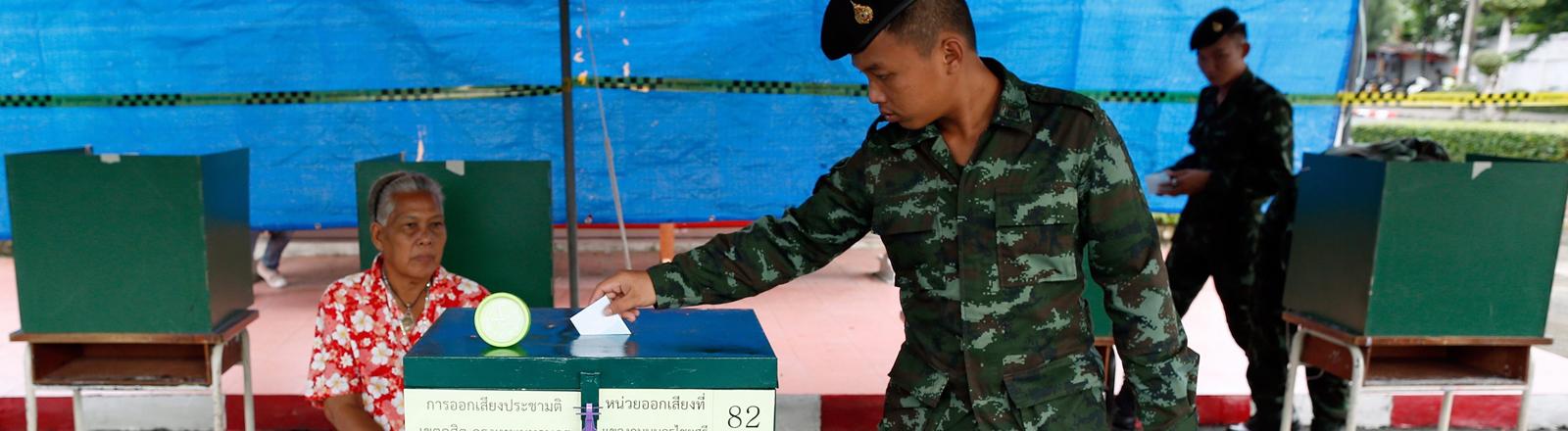 Ein Soldat in Uniform stimmt über die neue Verfassung in Thailand ab.