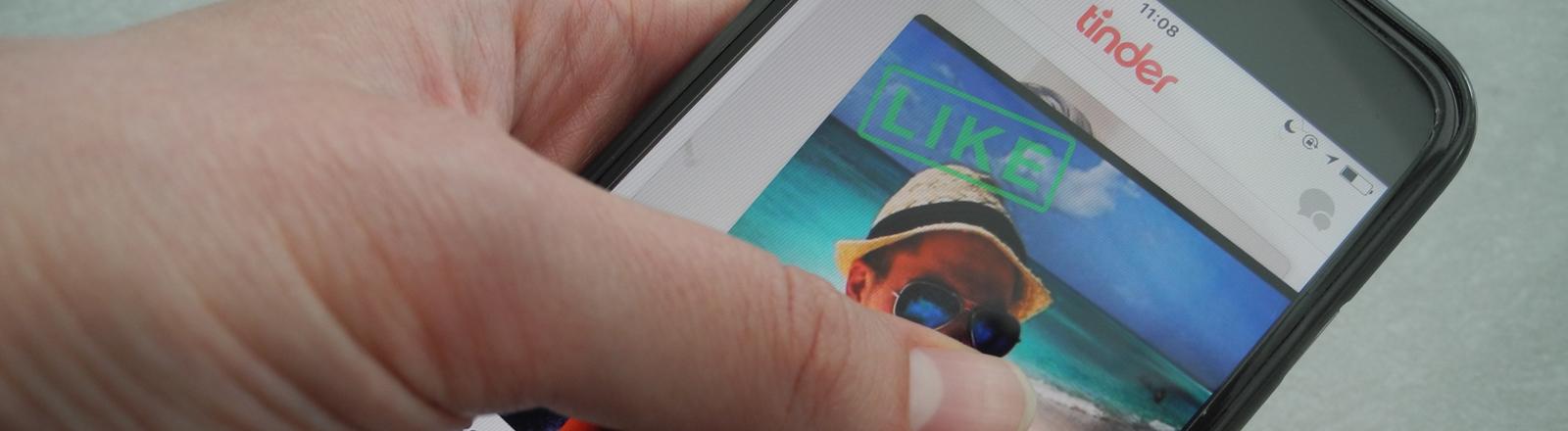 Ein Nutzer hält ein Smartphone auf dem die App Tinder läuft.