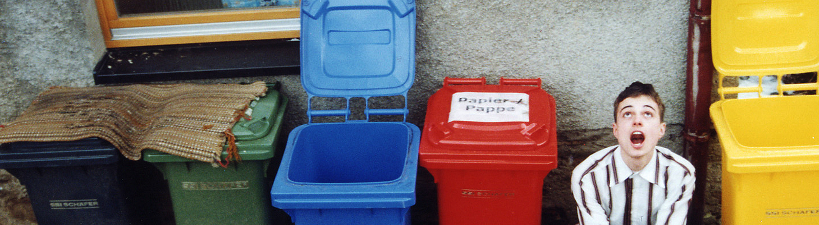 Ein Mann sitzt neben Mülltonnen