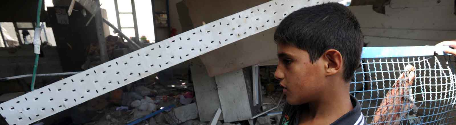 Ein Junge in einer zerstörten Schule im Gazastreifen