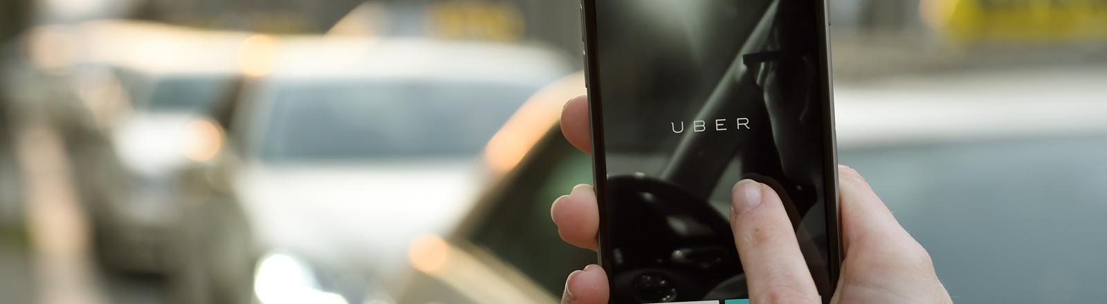 """Auf Display eines iphone 6 ist 20.03.2015 die Startseite der Apps """"Uber"""" vor einem Taxi-Stand zu sehen. """"Uber"""" ist ein Online-Vermittlungsdienst zur Personenbeförderung (z.B. Taxi)."""